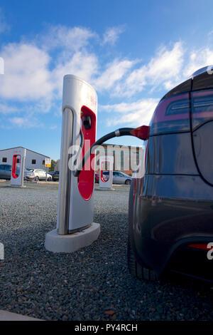 Charging car at Tesla. Electric charging point, UK - Stock Photo