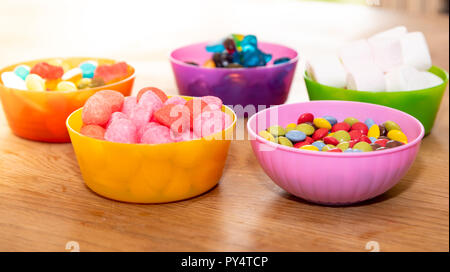 Full of candy in plastic bowls - Stock Photo