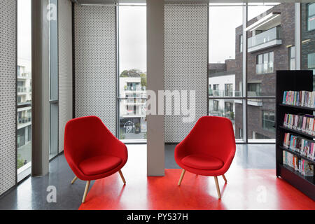 Red chairs and flooring and bookshelf on upper floor with rooftop view. ARhus Knowledge Centre, Roeselare, Belgium. Architect: B2Ai, 2014. - Stock Photo