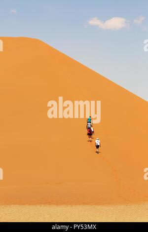 People climbing sand dunes, Sossusvlei, Namib Desert, Namibia Africa - Stock Photo
