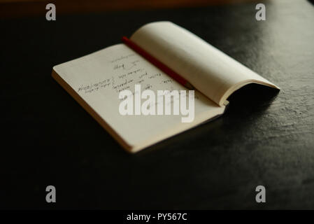 a notebook and a pencil on a table - Stock Photo