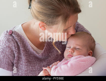 Mother holding her baby girl kissing her forehead close up with baby's eyes closed. - Stock Photo