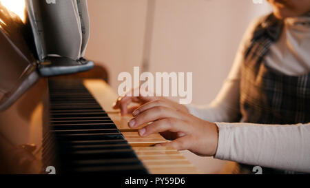 A baby playing piano on music lesson. Music notes on the music stand