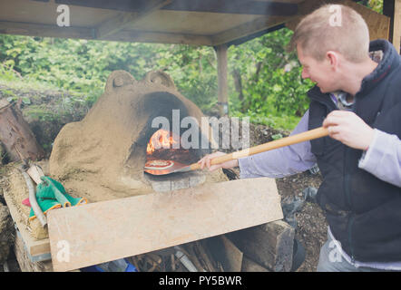 Handmade pizza being cooked on a home made outdoor pizza over in Bristol, England, UK - Stock Photo
