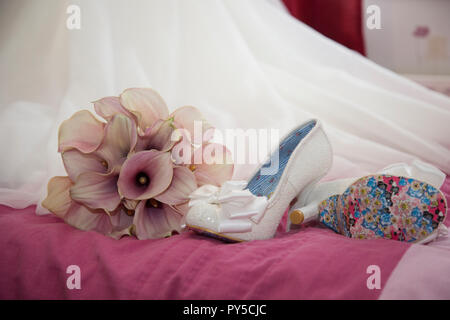 Brides shoes on the bed next to her bouquet of pink calla lilies sitting on the end of her wedding dress train waiting to be worn on her wedding day - Stock Photo