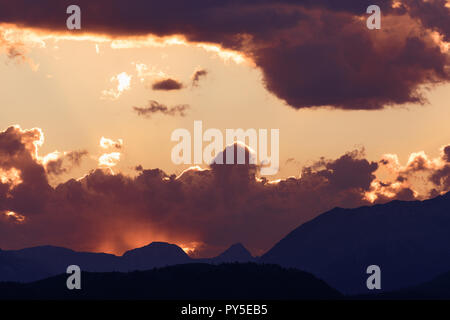 Sun peaks out from behind the clouds over Crowsnest Mountain and Seven Sisters Mountain - Stock Photo