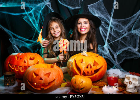 Halloween Concept - beautiful caucasian mother and her daughter in witch costumes celebrating Halloween with Halloween candy and sweet over spider web - Stock Photo
