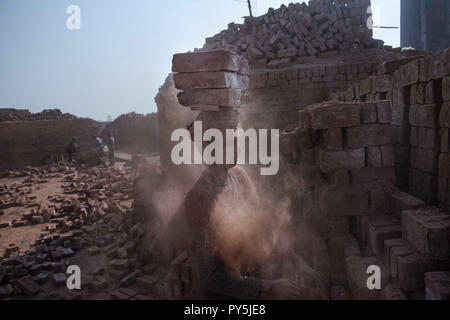 Narayanganj, Narayanganj, Bangladesh. 11th Mar, 2018. A man seen amidst dust carrying bricks on his head as he transfers them to another place at the brick field.Bangladesh is one of the developing country in recent days, where the industries, houses and mills everything is growing rapidly, in this era the demand for the bricks is too high and yet people are still making bricks in a traditional way and mostly the workers, who work in these brick factories are brought from the north parts of Bangladesh. These are internal migrated workers and they come hoping to make more money than in their - Stock Photo