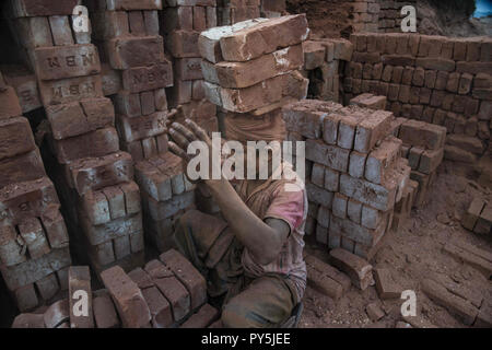 Narayanganj, Narayanganj, Bangladesh. 17th Mar, 2018. A man seen carrying bricks on his head transferring them to another place at the brick field.Bangladesh is one of the developing country in recent days, where the industries, houses and mills everything is growing rapidly, in this era the demand for the bricks is too high and yet people are still making bricks in a traditional way and mostly the workers, who work in these brick factories are brought from the north parts of Bangladesh. These are internal migrated workers and they come hoping to make more money than in their villages, gene - Stock Photo