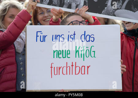 25 October 2018, Saxony-Anhalt, Magdeburg: Participants of the demonstration against the planned amendment of the Child Support Act (Kifög) protest with a poster on which 'For us the new Kifög is terrible' can be read. Several hundred parents and educators took part in the demonstration. The Kifög is currently being debated by the Landtag. The governing coalition of CDU, SPD and Greens had struggled for a long time to reach a compromise. One of the most important elements is that parents of several children will in future only pay childcare fees for the oldest child. Photo: Klaus-Dietmar Gabbe - Stock Photo