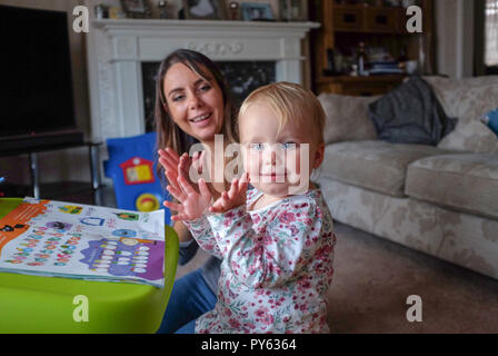 Young two year old baby toddler girl with her mother playing at home - Stock Photo