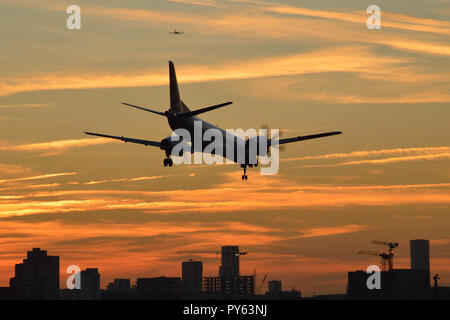 A small turbo-prop passenger plane comes in to land at London City Airport at sunset - Stock Photo