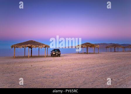 Car at palapa on beach after sunset at Campo Rancho Grande, Baja California, Mexico - Stock Photo