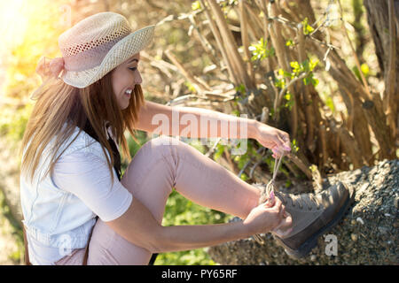 Beautiful young hiker tying her boots in the woods while smiling - Stock Photo