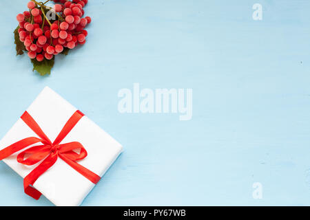 new year's gift and red berries on a blue Christmas background - Stock Photo