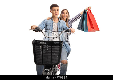 Teenage boy and girl riding on a bike, the girl holding shopping bags isolated on white background - Stock Photo