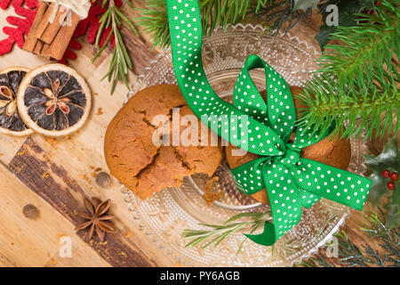 Cookies tied with green ribbon and Christmas decoration, on wooden surface. - Stock Photo