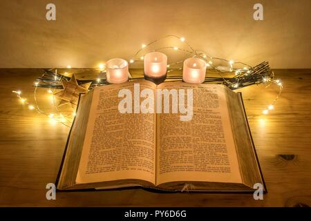 Old German Bible decorated with candles on a wooden desk - Stock Photo
