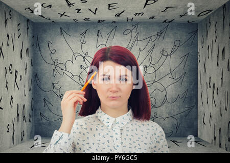 Puzzled businesswoman having questions in front of a a closed room with letters on walls  with a mess in her head  with difficult quest way with obsta - Stock Photo
