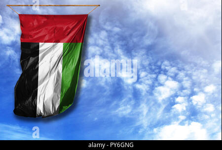 Flag of United Arab Emirates. Vertical flag, against blue sky with place for your text - Stock Photo