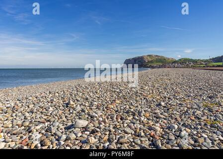 A view of Llandudno's curving shoreline with houses nested by a headland. The Little Orme is in the distance and a blue sky with clouds is above. - Stock Photo