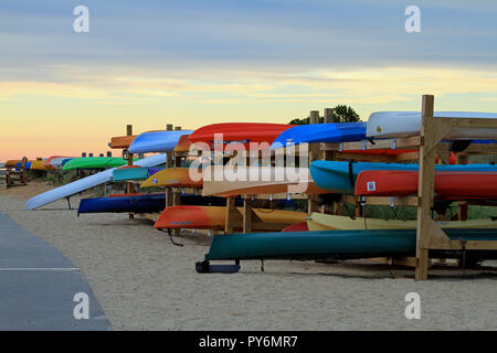 Colorful kayaks stored on wooden racks at Paine's Creek Beach and Landing in Brewster, Massachusetts, on Cape Cod - Stock Photo