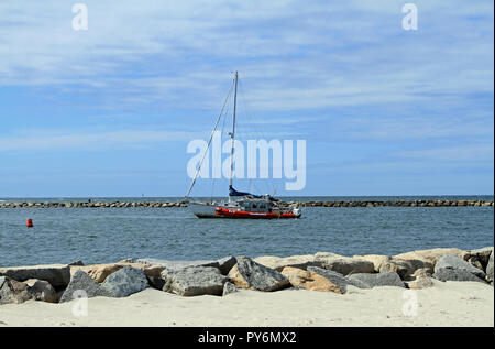 A disabled sailboat being pulled by a TowBoat U.S. through the jetty marking the entrance to Sesuit Harbor on Cape Cod in East Dennis, Massachusetts - Stock Photo