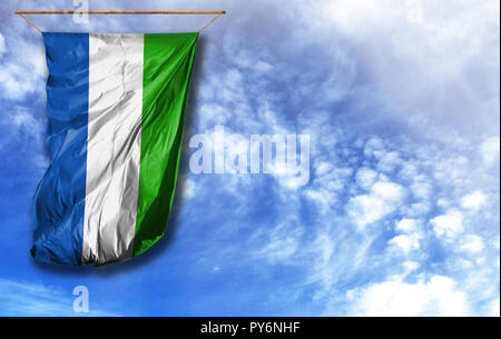 Flag of Sierra Leone. Vertical flag, against blue sky with place for your text - Stock Photo