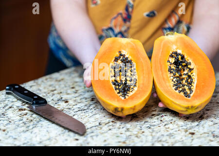 Closeup of female, woman hands showing, holding two halves ripe, ripened, fresh, orange papaya fruit slices with seeds sliced, cut in half on kitchen  - Stock Photo