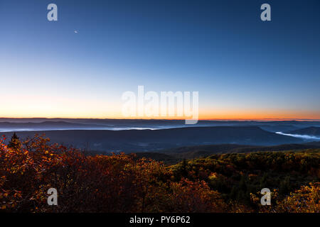 Bear rocks overlook during sunrise, dawn, moon in autumn with rocky landscape in Dolly Sods, West Virginia with orange foliage trees, blue, yellow sky - Stock Photo
