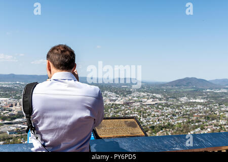 Roanoke, USA - April 18, 2018: Cityscape Skyline view of city in Virginia during spring with person, man tourist photographing mountains - Stock Photo