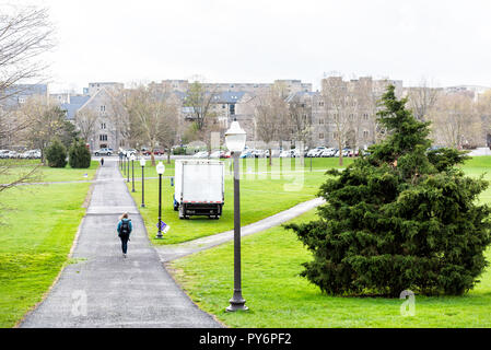 Blacksburg, USA - April 19, 2018: Historic Virginia Tech Polytechnic Institute and State University College campus with person walking on green grass  - Stock Photo