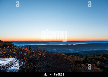 Bear rocks overlook sunrise, dawn, moon in autumn with rocky landscape in Dolly Sods, West Virginia with orange foliage trees, blue, yellow sky, layer - Stock Photo