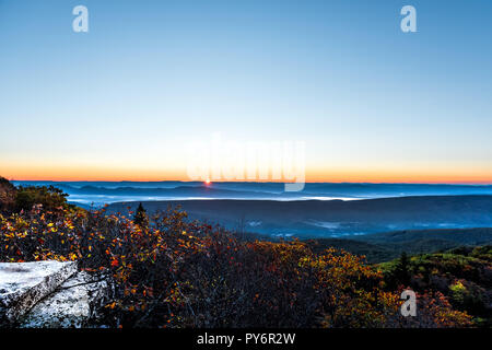 Bear rocks overlook sunrise, sunburst, sunrays, rays, sun behind mountains in autumn with rocky landscape in Dolly Sods, West Virginia with orange, ye - Stock Photo