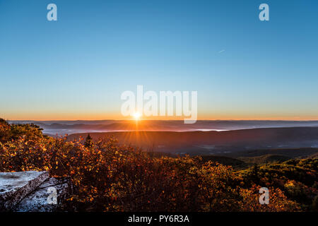 Bear rocks overlook sunrise, sunburst, sunrays, rays, sun above mountains in autumn with rocky landscape in Dolly Sods, West Virginia with orange, yel - Stock Photo