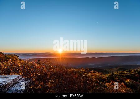 Bear rocks overlook sunrise, sunburst, sunrays, rays, sun above mountains in autumn with rocky landscape in Dolly Sods, West Virginia with orange, yel - Stock Photo