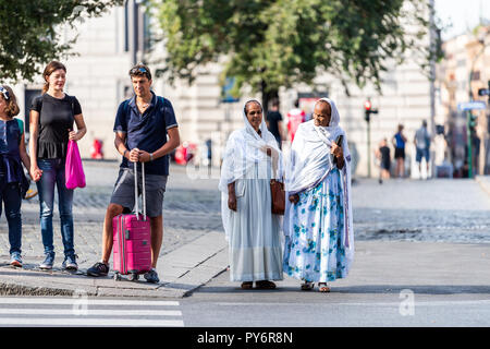 Rome, Italy - September 4, 2018: Family, couple tourists, Ethiopian African women walking in city town waiting to cross street - Stock Photo