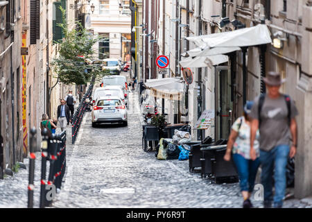 Rome, Italy - September 4, 2018: Streetscape of narrow city town road Via street in Rioni Trevi neighborhood, steep, cafe restaurant, people walking,  - Stock Photo