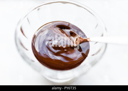 Closeup of spoon, mixing, stirring raw vegan liquid, creamy, smooth hot melted chocolate mousse, cream, icing syrup sauce in small glass bowl, dish - Stock Photo