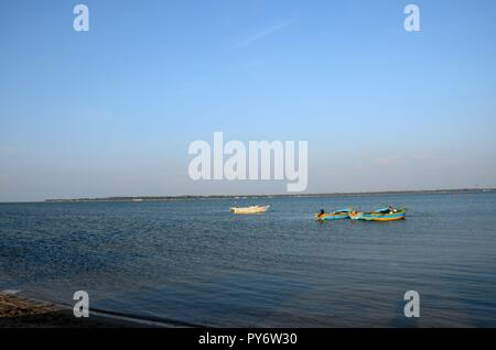 Several blue and yellow boats moored anchored in waters of Jaffna Sri Lanka - Stock Photo