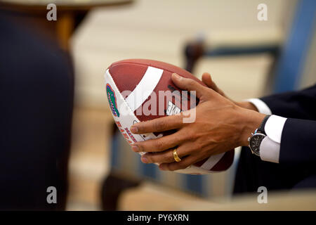 President Barack Obama holds a football during an Oval Office briefing for an upcoming healthcare meeting  May 11, 2009. Official White House Photo by Pete Souza.  This official White House photograph is being made available for publication by news organizations and/or for personal use printing by the subject(s) of the photograph. The photograph may not be manipulated or used in materials, advertisements, products, or promotions that in any way suggest approval or endorsement of the President, the First Family, or the White House. - Stock Photo