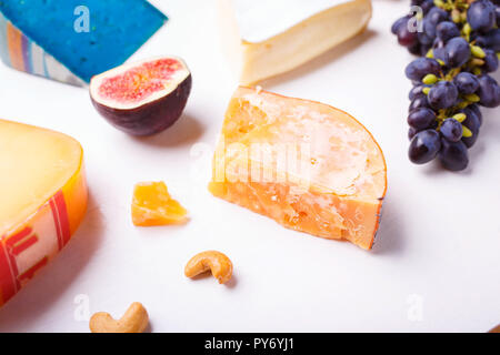 Variety of different cheese with nuts and grapes on the table. Top view image of soft and hard cheeses - Stock Photo
