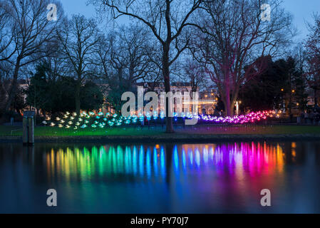 Colorful night in Amsterdam, Wertheimpark during the Amsterdam Light Festival with the artwork On the Wings of Freedom of Aether & Hemera. - Stock Photo