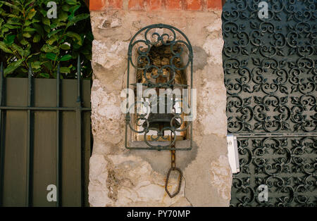 Vintage bell on the wall in the southern European city - Stock Photo