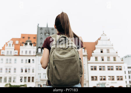 Tourist girl with backpack or student in Leipzig Square in Germany admiring beautiful buildings or architecture. Traveling in Germany. - Stock Photo