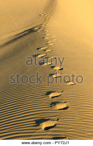 Fotprints in the sand lead away from viewer along a ridge of a sand dune in California's Algodones Dunes - Stock Photo