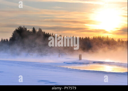 Mist over freezing river on a cold winter. Sunset view.