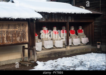29.12.2017, Takayama, Gifu, Japan, Asia - A row of Jizo statues made of stone, wearing red hats and bibs is seen sitting under a wooden shelter. - Stock Photo