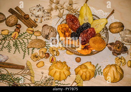 Dried frui in crystal rosette, nuts, pistachio, hazelnut, with eclairs, cinnamon surrounded by dried plants and shells on a figured shaped napkin - Stock Photo