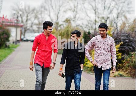 Three indian guys students friends walking on street.